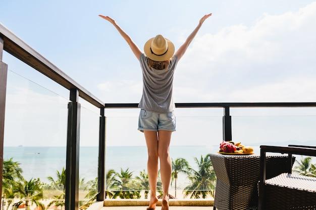 Happy woman back at hotel resort terrace