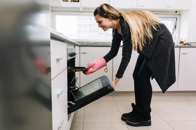 Happy woman baking cookies in oven