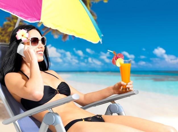 Donna felice sulla spiaggia che chiama dal telefono cellulare.