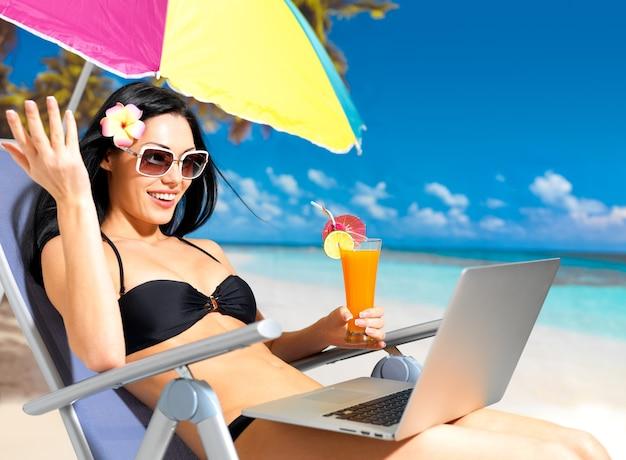 Donna felice sulla spiaggia con un computer portatile.