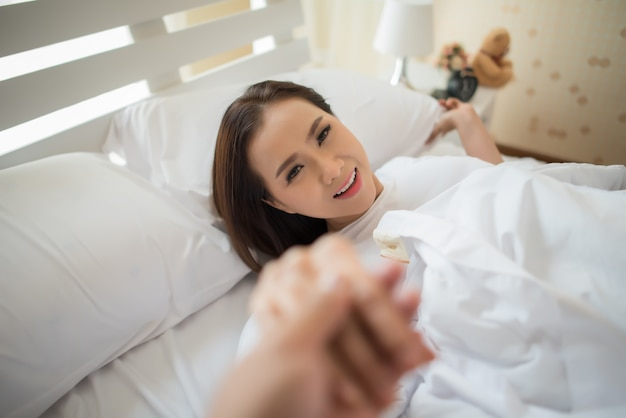 Happy woman on the bed and invited her boyfriend make something