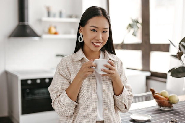 Happy woman in beige cardigan and white t-shirt smiles sincerely and drinks coffee on kitchen