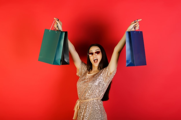 Happy woman in beige dress with sequins and red eyeglasses hold colorful bags with purchases isolated on red