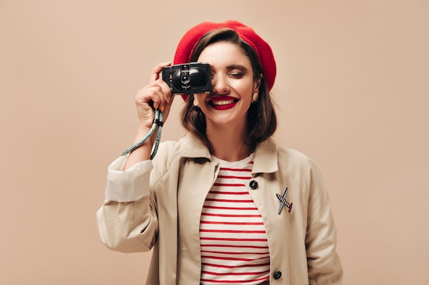 Happy woman in beige outfit holds black camera. joyful young girl in striped sweater and light coat makes photo on isolated backdrop.