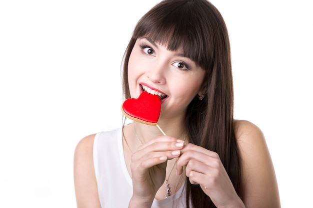 Happy woman biting heart shaped biscuit