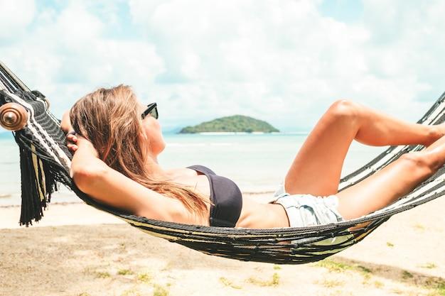 Happy woman in black bikini relaxing in hammock