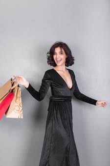 Happy woman in black dress with shopping bags