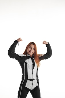 Happy woman in black and white protective motorbike apparel with hands up