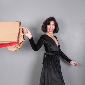 Happy woman in black with shopping bags