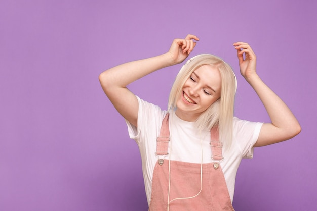 행복 한 여자 금발 여자는 눈을 감고 헤드폰에서 음악을 듣는