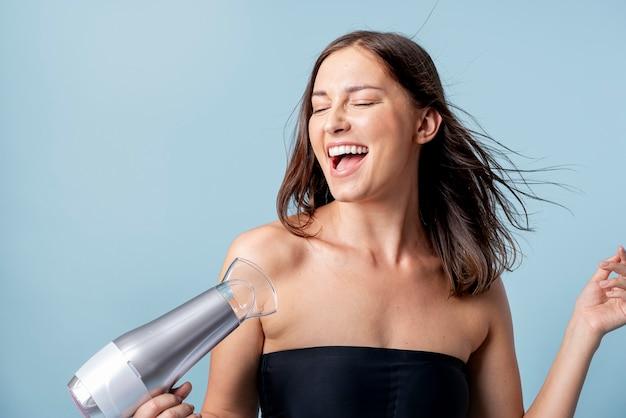 幸せな女性は彼女の髪を乾かすブロー