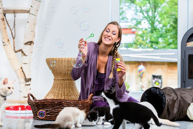 Happy woman blowing bubbles while kittens are drinking milk