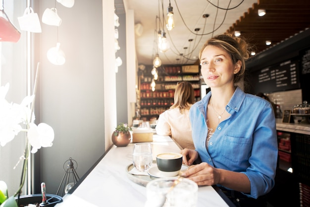 Happy woman in blue shirt in a coffee shop