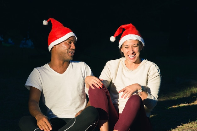 Happy woman and brazilian man enjoying sun rays with red christmas hats young couple on sunlight