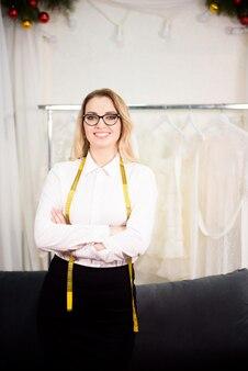 彼女のテーラーショップで幸せな女性のビジネスオーナー。居心地の良い職場、リモートワーク、ビジネスコンセプト。