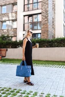 도시 거리 배경에 가방과 드레스를 입은 안경을 쓴 행복한 여성 사업가