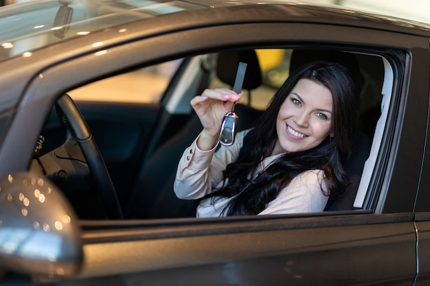 Happy woman buyer examines her new vehicle in car dealership