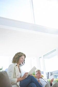 Счастливая женщина человеком с помощью цифрового планшета