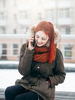 冬の路上で携帯電話で呼び出す幸せな女性