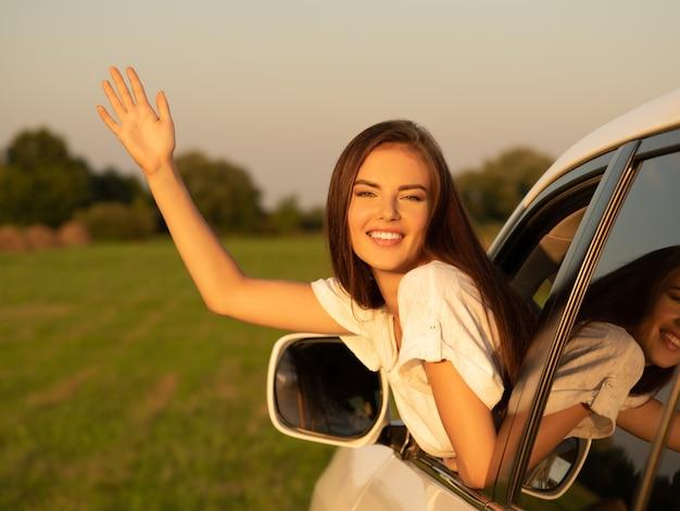 Donna felice in macchina con la mano alzata.