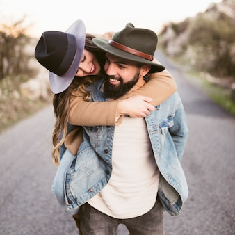 Happy woman carried on boyfriend back