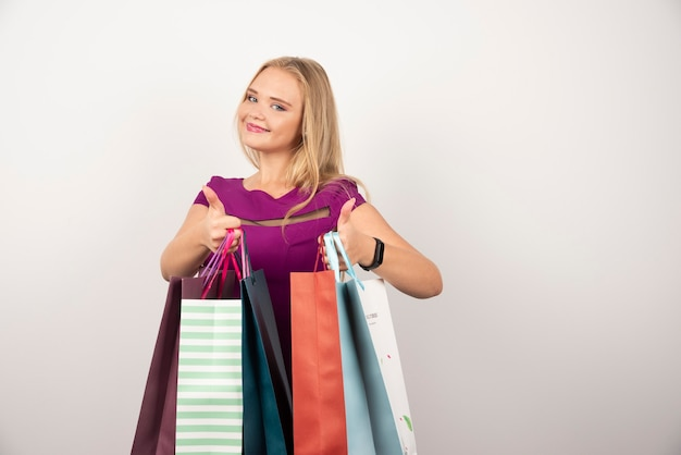 Happy woman carrying colorful shopping bags and making thumbs up.