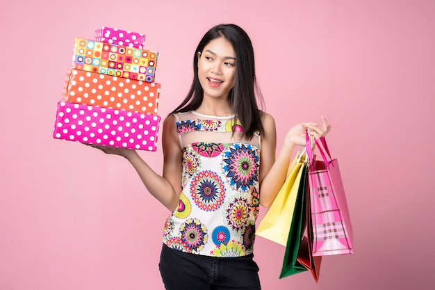 Happy woman carrying gift boxes and shopping bags