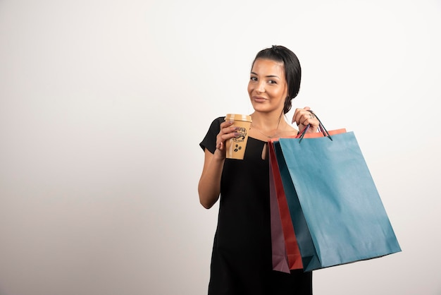 Happy woman carrying shopping bags and coffee on white wall.