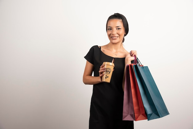 Happy woman carrying shopping bags and coffee.