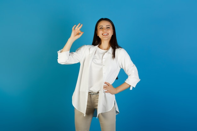Happy woman in casual clothes gesturing ok on blue