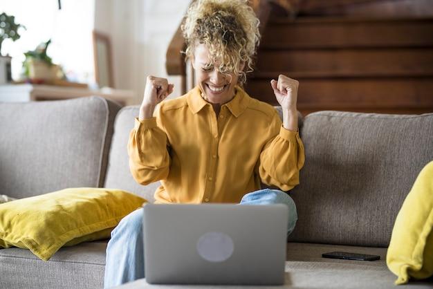 幸せな女性は、自宅のソファに座っているラップトップコンピューターの前で祝い、歓喜します-勝利とオンライン作業またはショッピングライフスタイルの概念-幸せな人々スマートワーキングオフィスの仕事