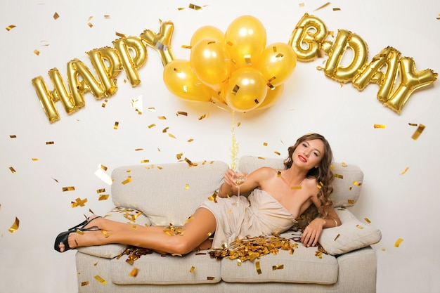 Happy woman celebrating birthday in golden confetti sitting on sofa