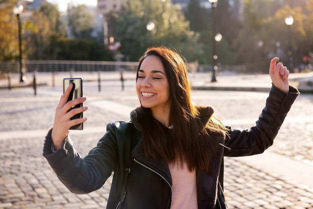Счастливая женщина празднует глядя по телефону
