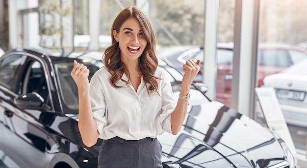 새 차 구입을 축 하하는 행복 한 여자