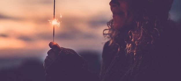 線香花火の光で屋外を祝う幸せな女性