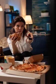 Счастливая женщина меняет каналы с помощью удаленного просмотра развлекательного фильма по телевидению