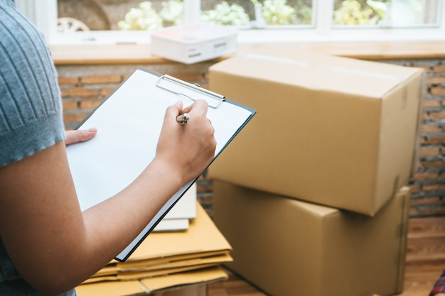 Happy woman checking stuff in cardboard box before sent to transportation company and movi