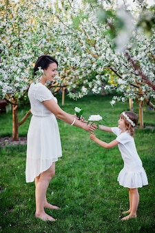 Happy woman and child, cute daughter and mother in blossom spring garden, wearing white dress outdoors, spring season is coming. mothers day holiday concept