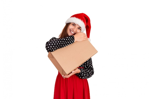 Happy woman in chistmas hat hugs a gift wrapped in recycled paper. isolated on white background. holidays