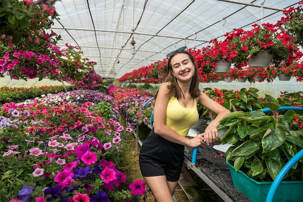 Happy woman chooses flowers in a greenhouse. botany
