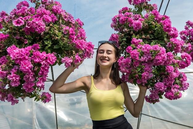 幸せな女性は温室で花を選びます。植物学