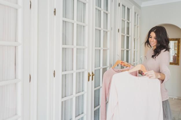 Happy woman choosing between two sweaters