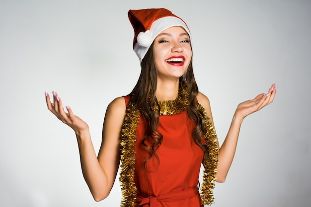 Happy woman in a christmas hat on a gray background