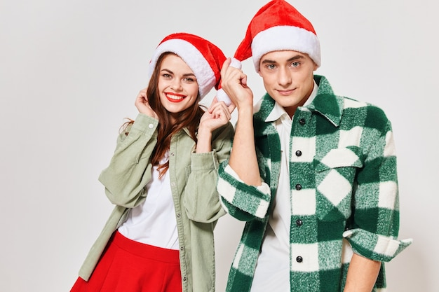 Happy woman in a christmas hat and a man in a plaid shirt on a light background. high quality photo