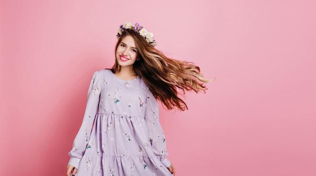 Donna felice in cerchietto di fiori in posa con agitando i capelli
