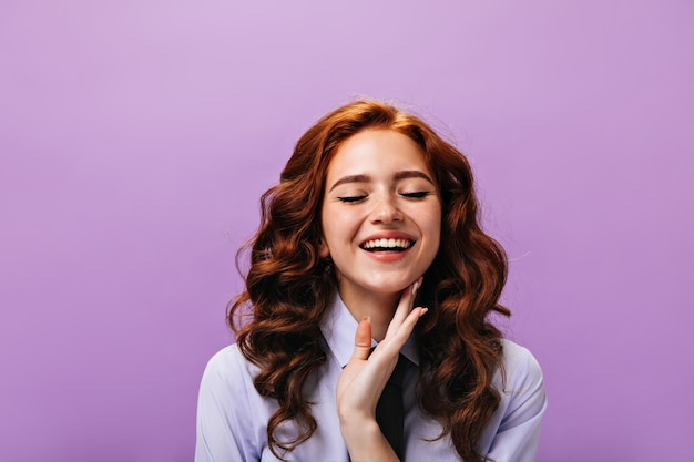Happy woman in classic style outfit smiling with closed eyes