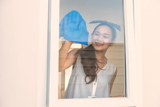 Счастливая женщина чистит окно нового дома