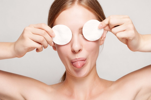 Happy woman cleaning her face with cotton pads