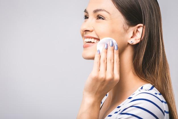 コットンパッドで顔を掃除する幸せな女性