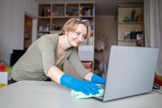 コンピュータからほこりを拭いて家を掃除する幸せな女性